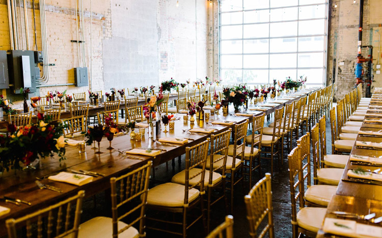 A beautiful banquet hall with fine wooden tables and chiavari chairs