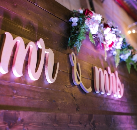 A wooden wall with a sign containing the words mister and missus underneath flowers.
