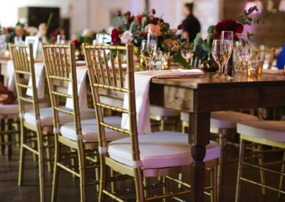 White and gold Chiavari chairs in front of an elegant wooden table.